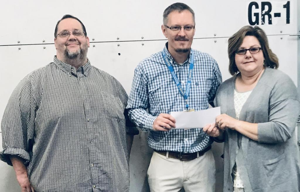 Center Walmark Manager Jeff Martin, center, presents a check to Sherry Harding, right, and Josh Crawford with Shelby County Outreach Ministries.