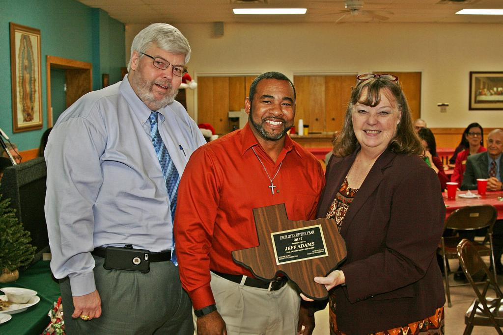 "DETCOG 9-1-1 Program Director Van Bush (left) and DETCOG President Lynn Torres (right) present Jeffrey Adams with the ""DETCOG Employee of the Year"" Award."