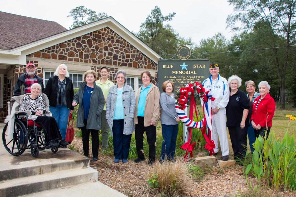 Larry Hume of VFW Post 8904 poses with members of the Center Garden Club in front of the Blue Star Memorial at the Community House in Center.