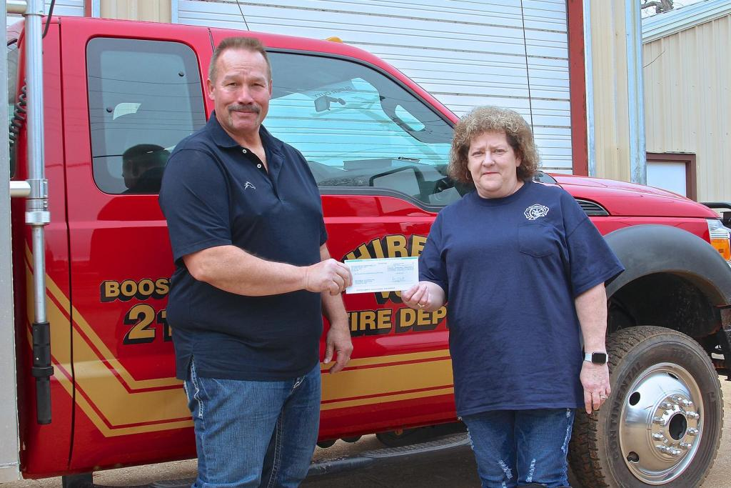 Aethon Energy's Kelly Tompkins, Texas District Foreman, left, presents a donation for the Chireno Volunteer Fire Department to Fonda Brewer,  a member of the fire department's team. The Chireno VDF is determining the equipment they will procure with the donation.