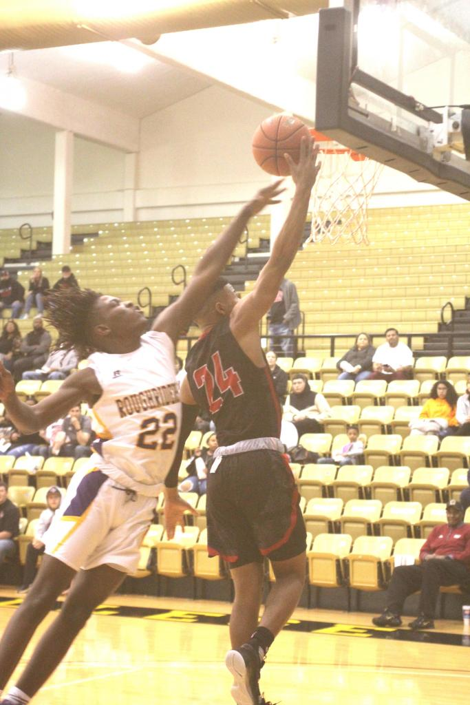 Jamarrion Evans, No. 22, works at tipping the ball away from a shot by a Mexia player.