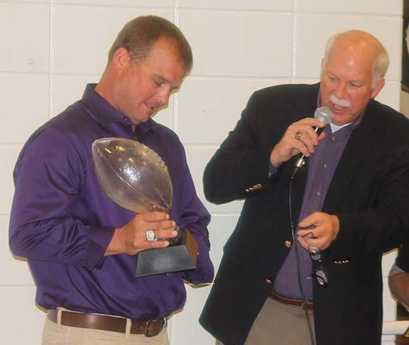 Kevin Magee receives a glass football trophy.
