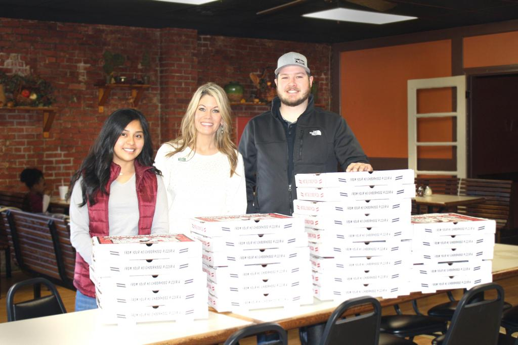 Maritza Cadena, Jane Bount and Collin Mathews are seen picking up boxes of fresh hot pizza to be delivered to area schools.