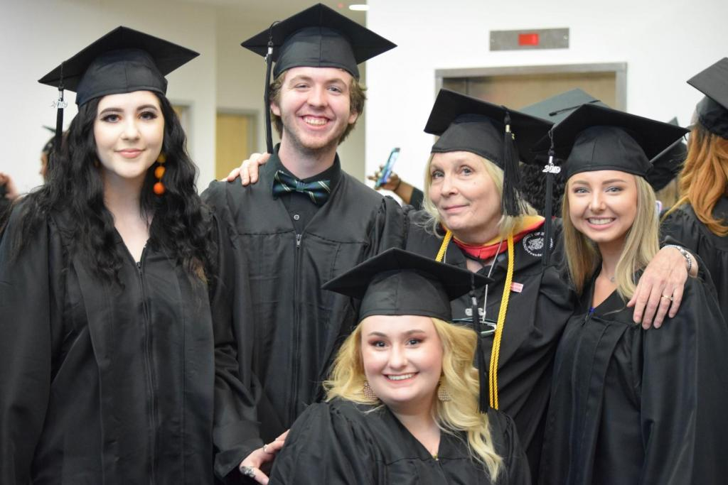 Theatre Professor, Karen King, takes a photo with a few of her students that graduated this spring.