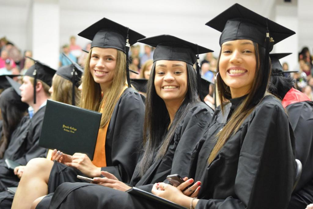 Students show off their diploma after walking across the stage at graduation.