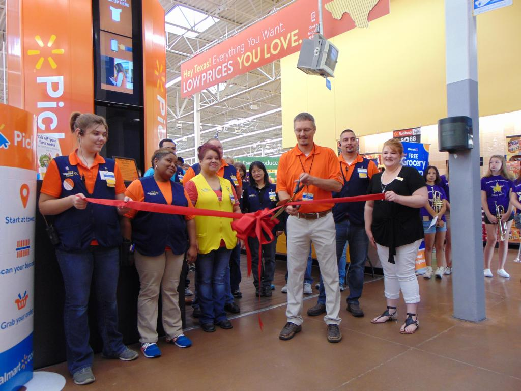 Center Walmart Store Manager Jeff Martin, with ceremonial scissors, prepares to cut the ribbon kicking off the store's new curbside grocery pickup service. Shelby County Chamber of Commerce Ambassador Chair Cindy Lindsey, holding ribbon right, was joined by Shelby County Chamber Ambassadors and chamber members along with Walmart associates and Center High School band members at the Tuesday ceremony.
