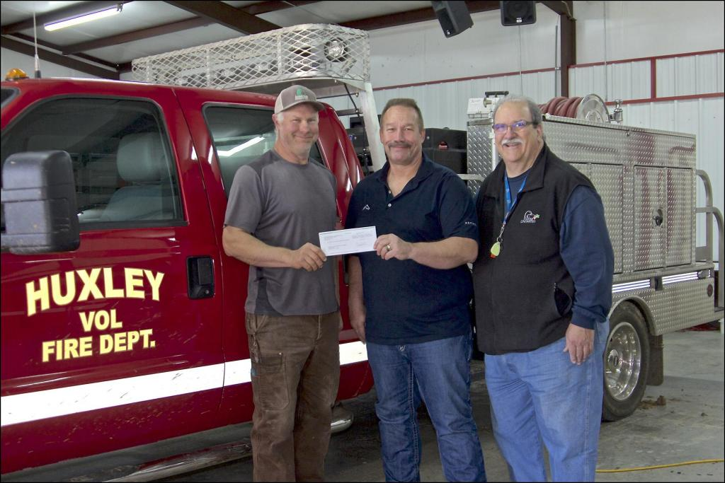 Aethon Energy's Kelly Tompkins, Texas District Foreman, center, presents a donation to J. E. Yazoo Thomas, right, and Huxley VFD Fire Chief Bob Vandrovec, for the Huxley Volunteer Fire Department. Vandrovec plans to purchase firefighting clothing called turnout gear with the funds.