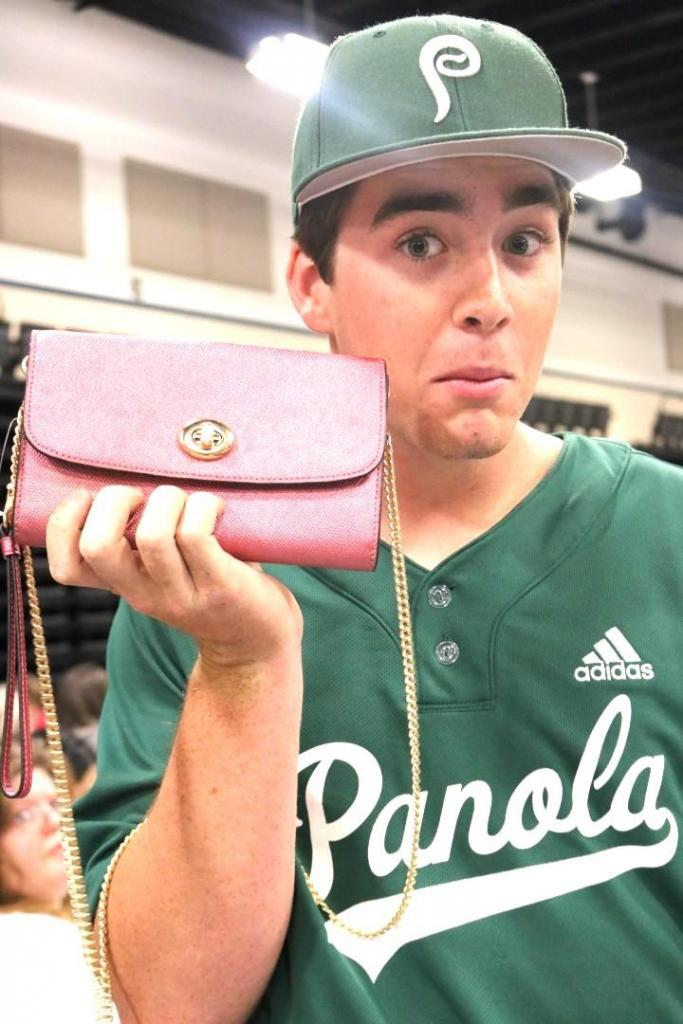 Panola College Baseball player shows guests one of the lovely purses available to win.