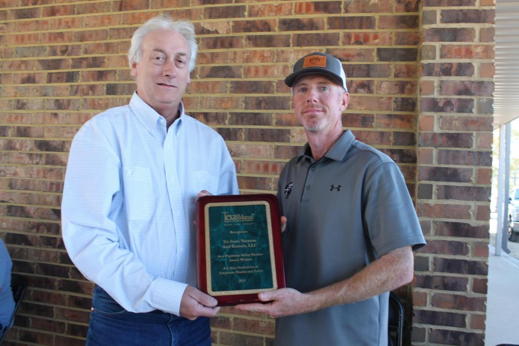 Texas Mutual's Rock Spraggins, left, presents Tri-State's Troy Massey with a plaque during a fall ceremony.