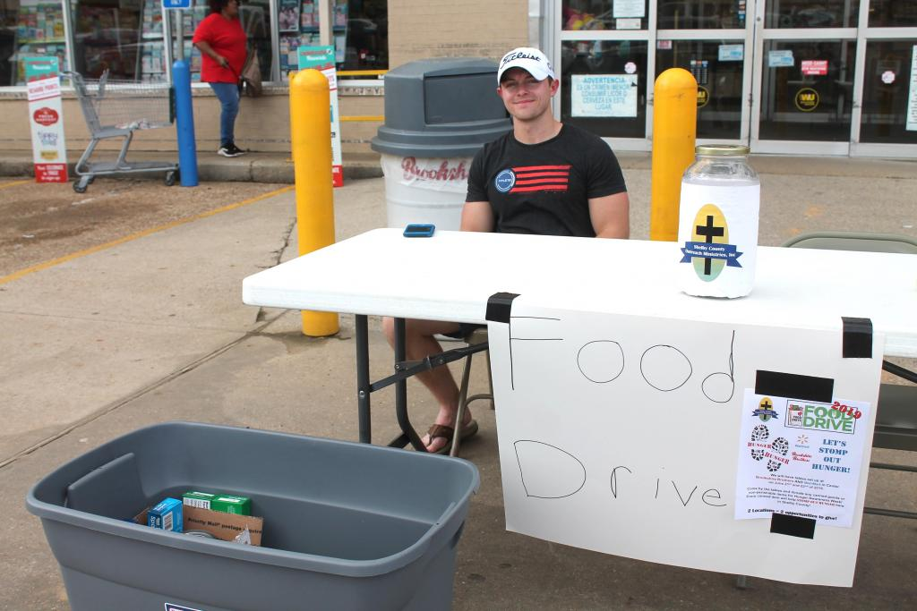 Grant Murphree manning food drive collection table at Brookshire's in Center on Friday.