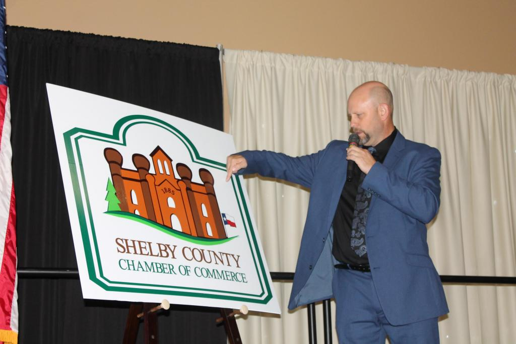 Emcee Chris Whatlington is seen with the new logo for the chamber which was unveiled by President Deborah Chadwick