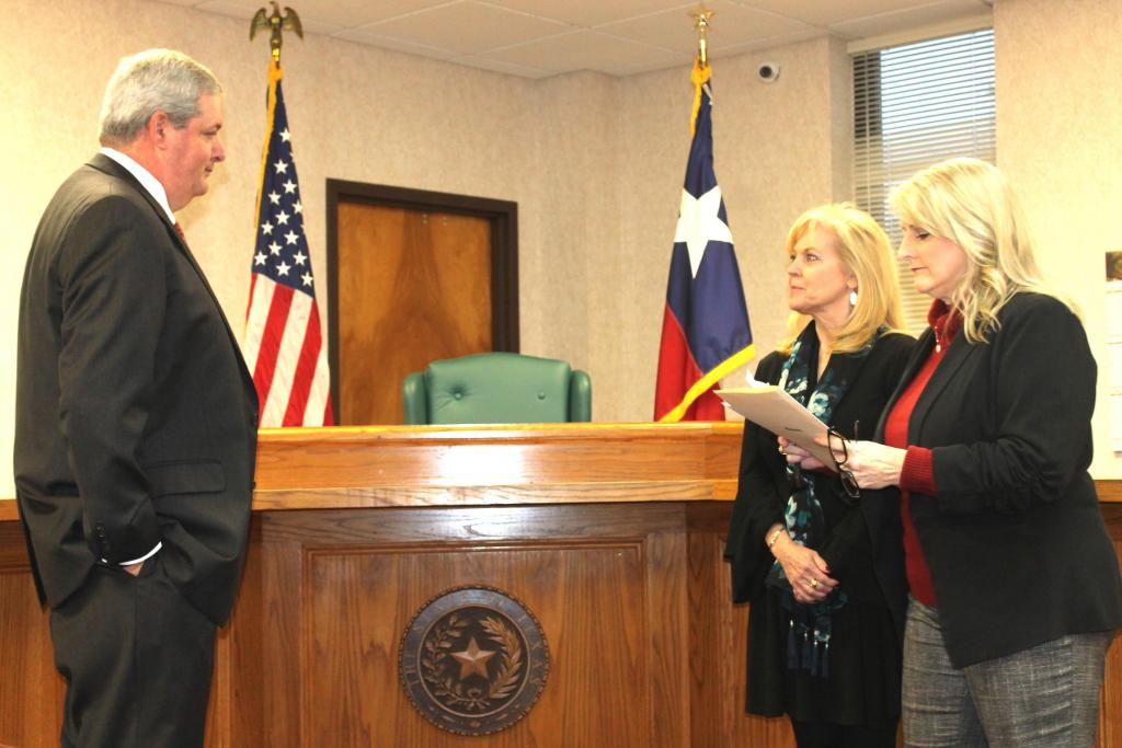 Judge Harbison, right, prepares to swear in newly elected District Judge James A. Payne, Jr., left, while wife Jill Payne, center, listens.