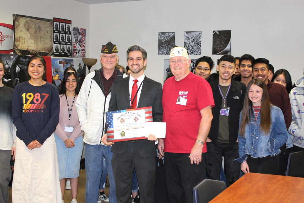 Nicholas Wheeler, center, on Thursday was presented a plaque as VFW Post 8904's Teacher of the Year. He is seen with VFW's Larry Hume, left, and Gene Hutto, right; and CHS students