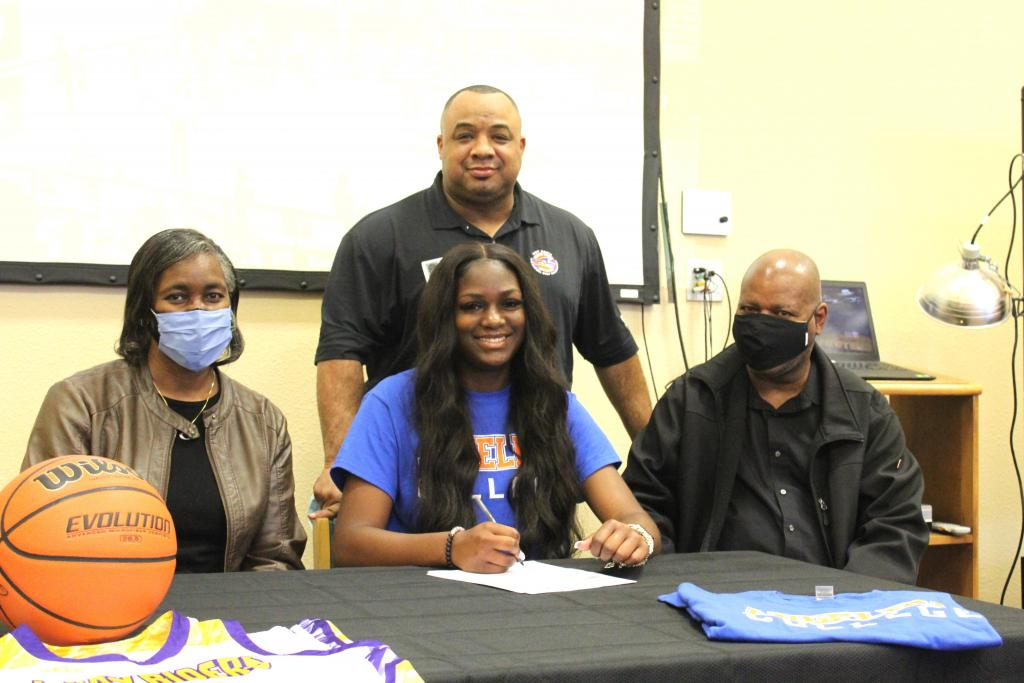 Center Lady Riders basketball standout Ja'Kayla Parks, seated center, was all smiles after signing a college letter to play for Angelina College. She us seen with grandparents Brenda and Martin Randle, and Angelina Coach Byron Coleman, standing.
