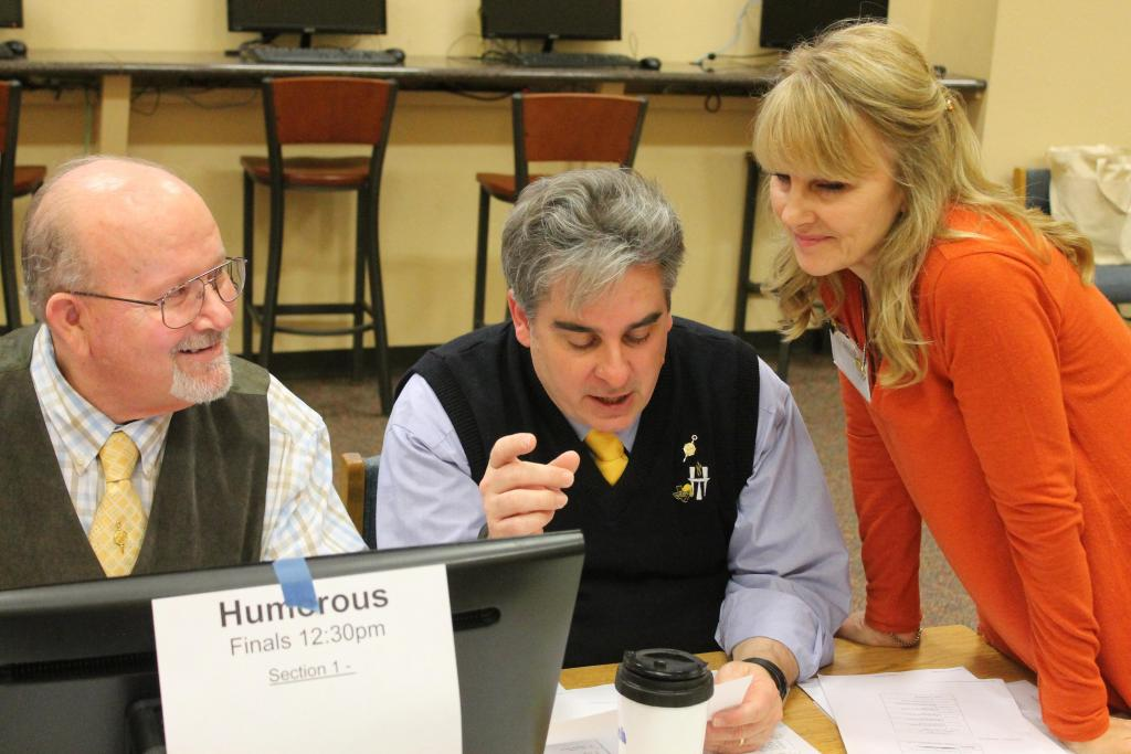 Donna Szumila, right, Yellow Rose District Debate Chair, looks over details of the weekend tournament held in Center with Jimmy Smith and Chris Mosmeyer on Friday afternoon. (Mike Elswick/The Light and Champion)