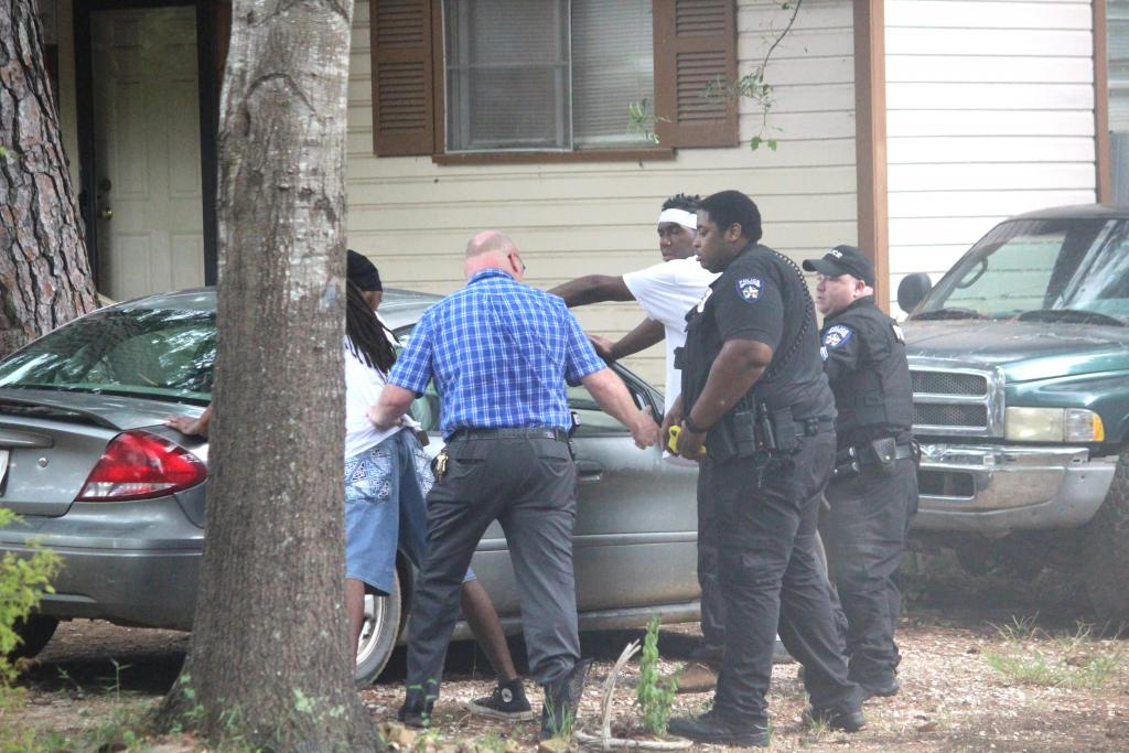 Lt. Jeremy Bittick, plaid shirt, places a suspect in handcuffs on Sampson Street Monday afternoon.