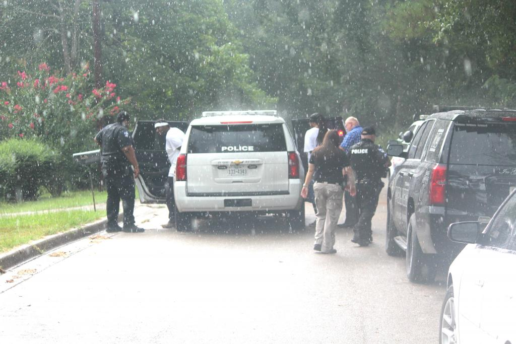 Heavy rain started falling as two suspects were placed in a CPD vehicle for transport.