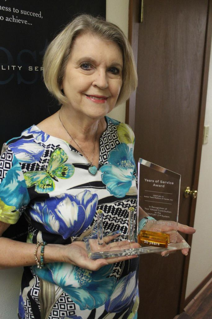 Century 21 Action Team Realtors of Center broker/owner Laura Rowe is seen with the award she was recently presented for 30 years of service to the Century 21 System.