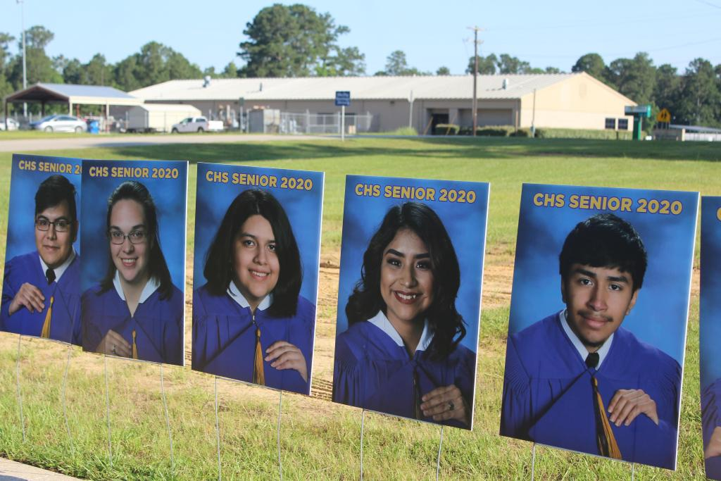 Yard signs featuring Center High School class of 2020 Seniors line Roughrider Drive.