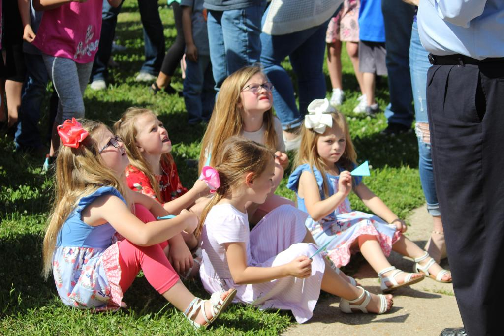 Young attendees at Tuesday's butterfly release look skyward as butterflies are individually released.