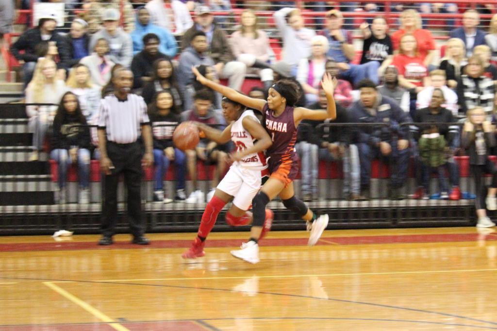 Senior JaKaitlon Bolton of Shelbyville pushes past Tenaha's Lucy Giles on her way to the basket. (Photo by Taylor Bragg, Freelance Photographer)