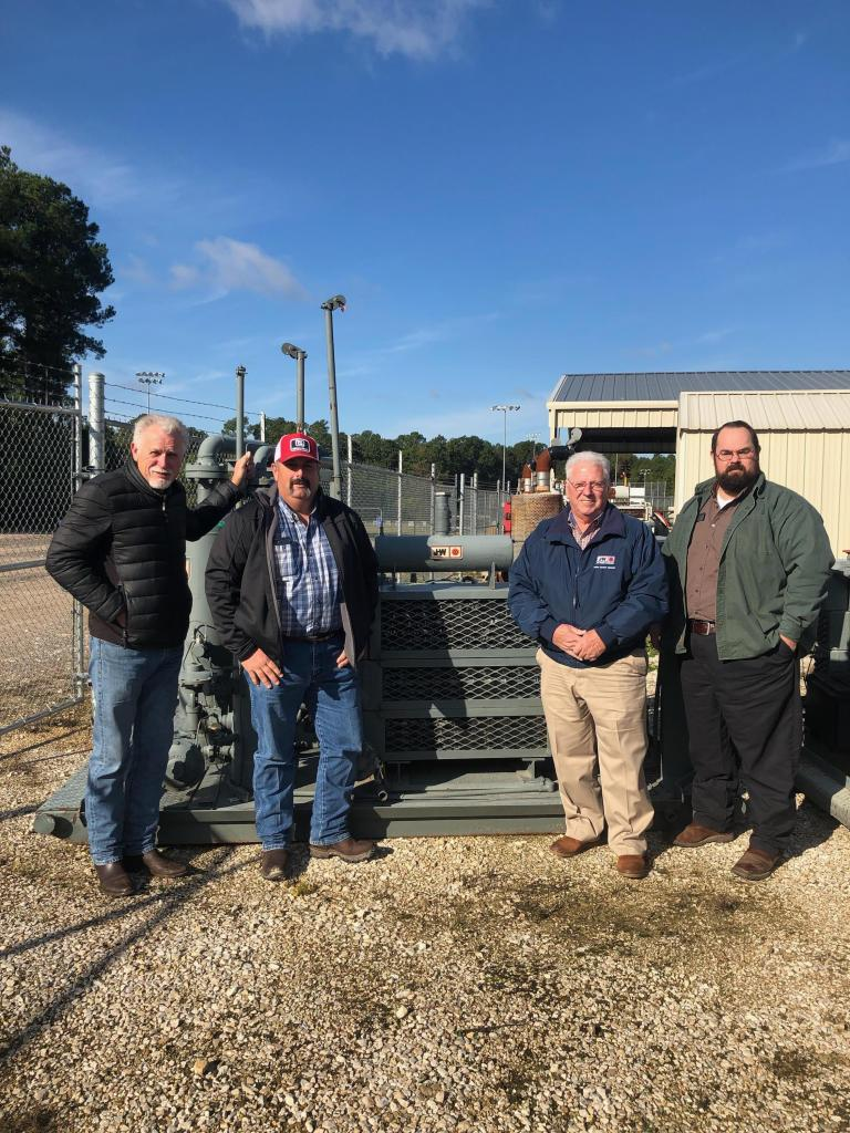 L to R) Jim Permenter, Steven Myers, Gary Hale, and Daniel Hall stand in front of one of the two donated compressors.