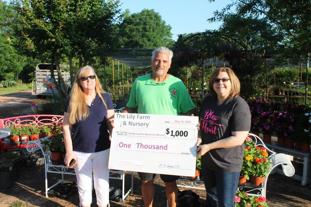 Meals On Wheels representatives Darlene Mitchell, left, and Sherry Harding, right, accept a $1,000 donation from Mark Carpenter, owner of The Lily Farm.