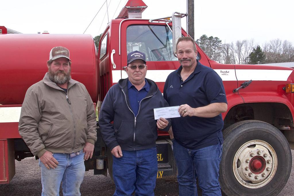 Aethon Energy's Kelly Tompkins, Texas District Foreman, left, presents a donation for the Martinsville Volunteer Fire Department Stephen Phillips, Martinsville VFD Fire Chief and firefighter Robert Phillips. The Martinsville VDF is working on its plan to use the additional funds.