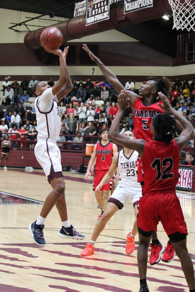 Michael Hogg of Tenaha attacks the basket with a short-range jump shot. The combined play of Hogg and Deuce Garrett gave the Tigers the spark they needed to send the tight ballgame into overtime. (Photo by Taylor Bragg, Freelance Photographer)