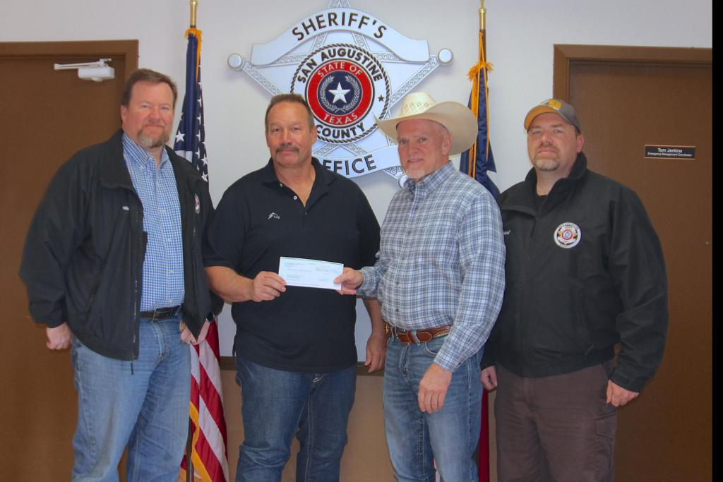 Aethon Energy's Kelly Tompkins, Texas District Foreman, second from left, presents a donation to San Augustine Sheriff Robert Cartwright, second from right, Chief Deputy John Welch, far left, and Lieutenant Shannon Brazeal. The sheriff's department plans to use the funds to purchase cell phone boosters to improve reception in remote areas for the safety of the officers and the public.