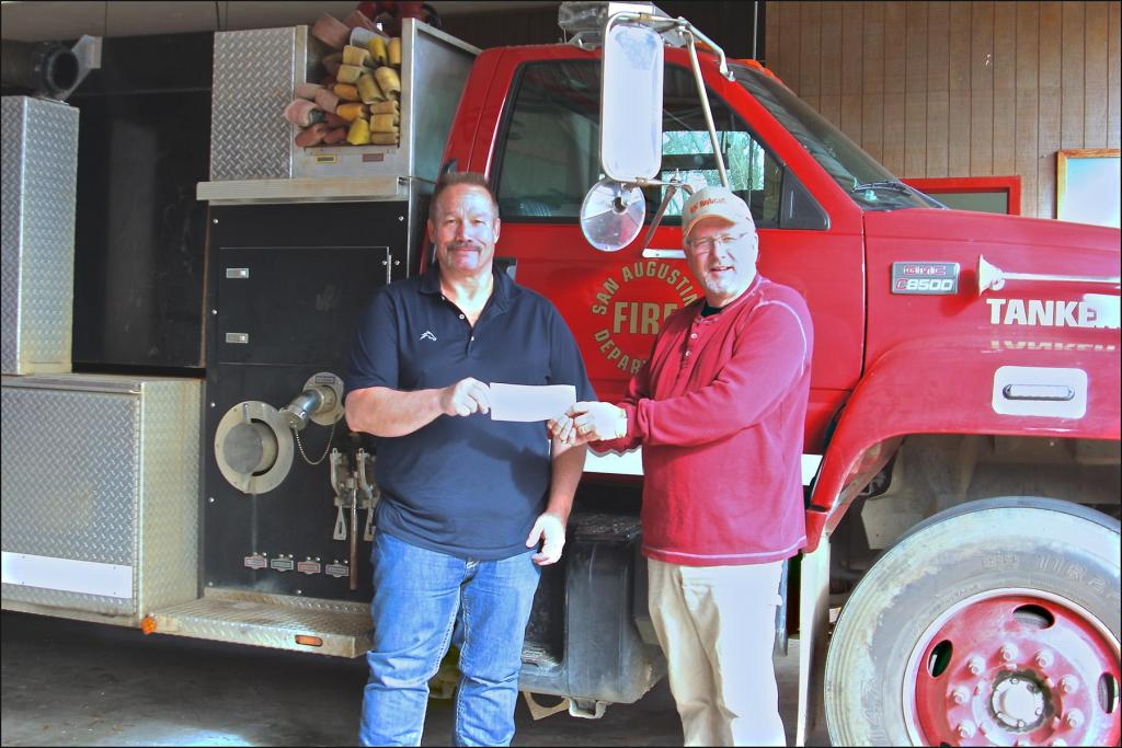 Aethon Energy's Kelly Tompkins, Texas District Foreman, left, presents a donation to Fire Chief Charles Sharp for the San Augustine County Volunteer Fire Department. The San Augustine VDF plans to purchase additional equipment for the team.