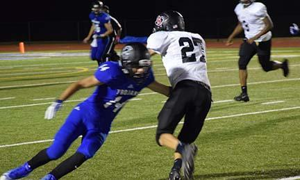 Kaleb Campbell (#27) makes All Saints LB Jay Baugh (#14) miss on a 7-yard run in the 2ndquarter